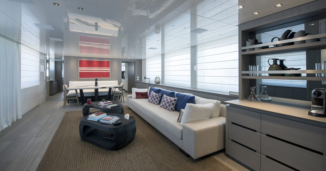 sofas, coffee table and dining table in the light, airy and modern main salon on board superyacht DINAIA