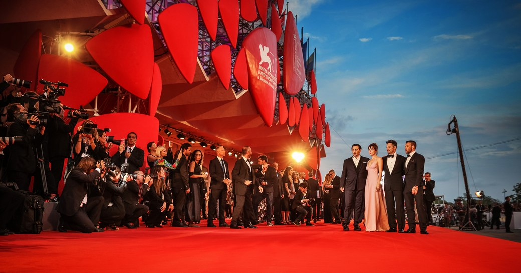 movie stars have their picture taken on the red carpet at the venice film festival