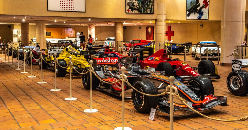 Racing cars inside the Collection de Voitures Anciennes in Monaco behind a rope barrier