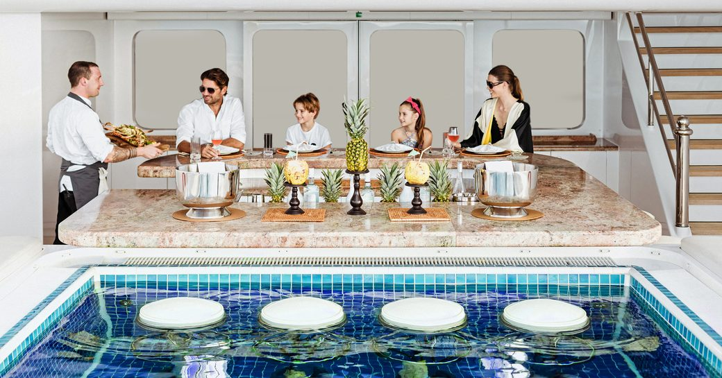 family is served meal overlooking pool on luxury yacht titania