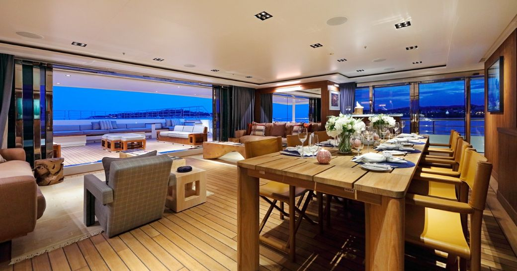 dining table and seating areas in the main salon aboard luxury yacht Planet Nine