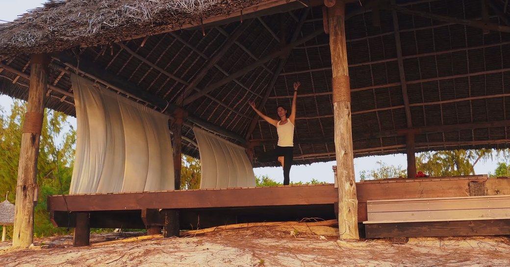 woman practises yoga on stage on thanda island
