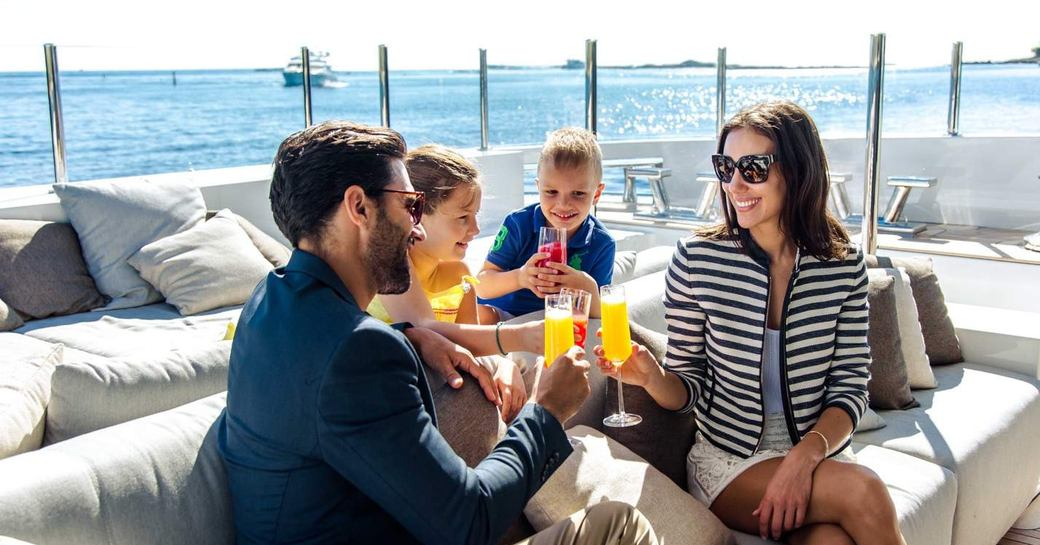 a family on a luxury yacht charter vacation enjoy some refreshments on their motor yacht after a safe journey to begin their charter in peace and tranquillity in the midst of a pandemic