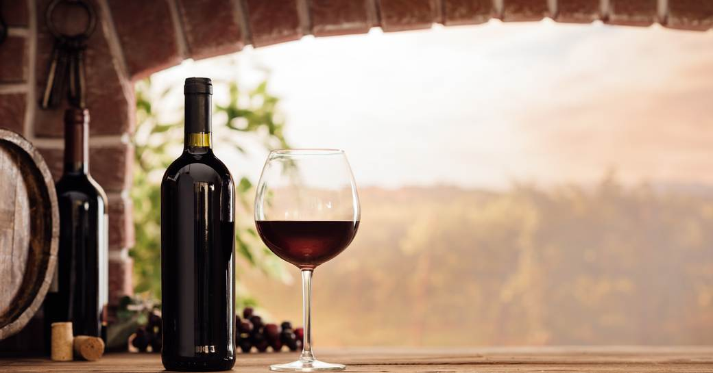 A bottle of red Cannonau wine from Sardinia next to a half-filled wine glass on a brick window ledge with a view of a vineyard