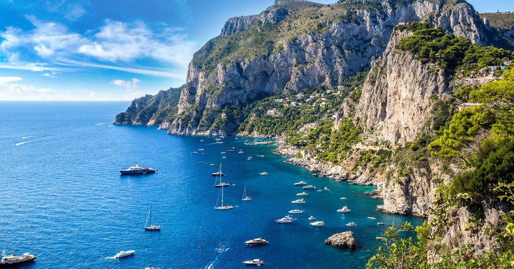 a shining fleets of superyachts off of the coast of capri with their guests enjoying the hot Mediterranean sun as they cruise from port to port on their Italy yacht charter adventure