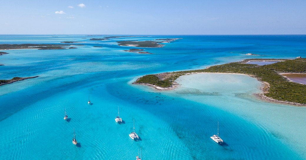 Beautiful clear waters and small islets with yachts around them in the Bahamas