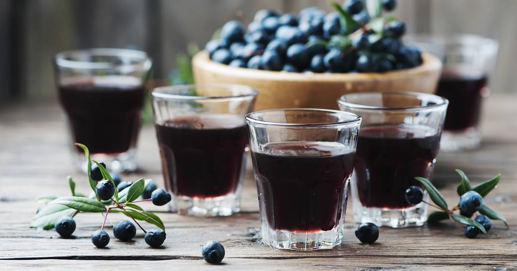 Four tumblers of red Sardinian mirto liqueur in front of a bowl of wild myrtle berries