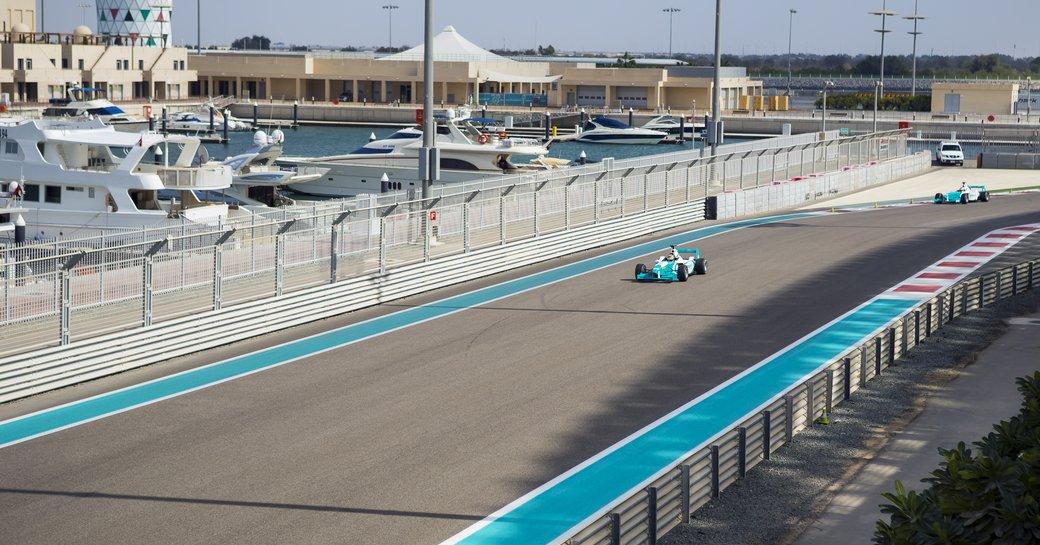 Formula 1 racer on Abu Dhabi Yas Marina Circuit, motor yachts berthed adjacent to track.