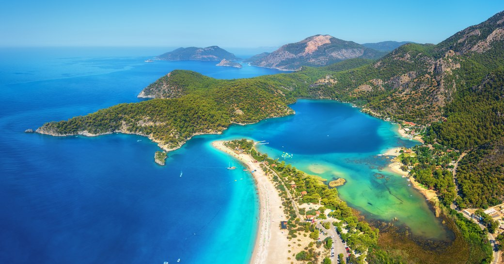 sandy beach in Turkey, with blue lagoon and green forests