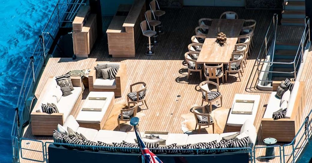 bar, seating areas and dining table on aft deck of luxury yacht 'Plan B'