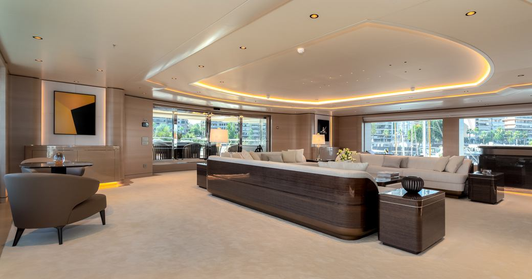 Large open plan room on superyacht O'PARI, three sofas visible on right and chair and small table on left with large windows all around