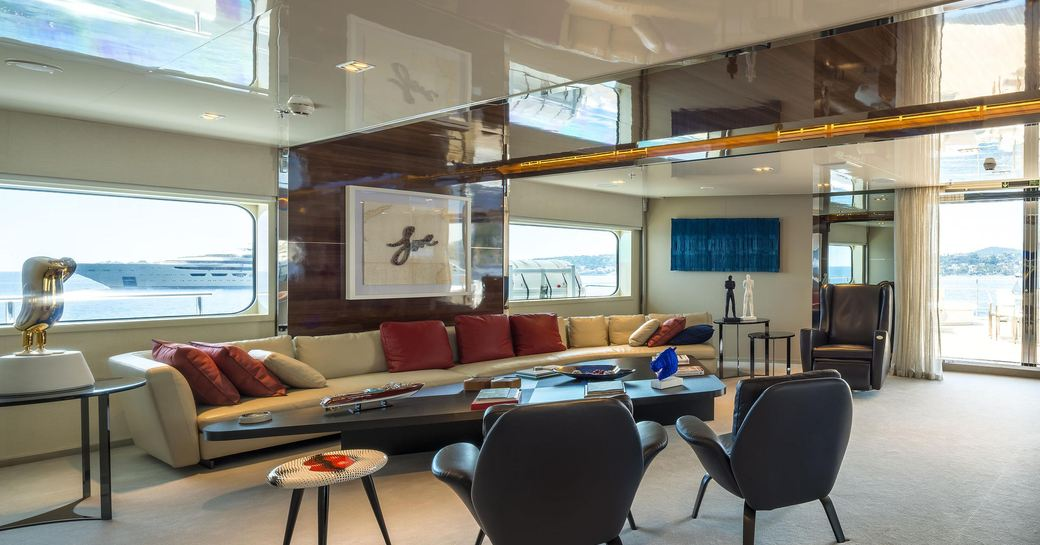 Main salon onboard M/Y SERENITY, long sofa along far wall, facing coffee tables and two armchairs