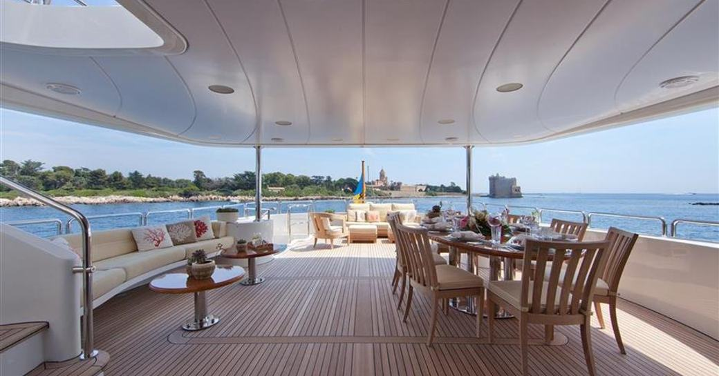 Upper deck of charter yacht BRUNELLO with formal alfresco dining and sofa seating