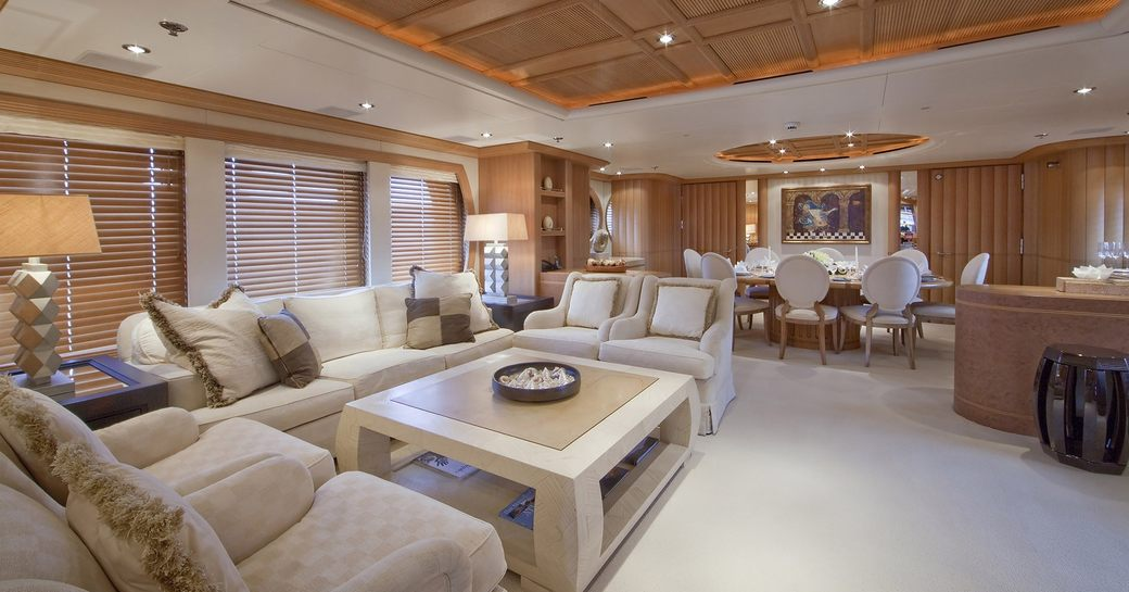 timeless main salon with sumptuous lounge and formal dining area on board charter yacht Deja Too