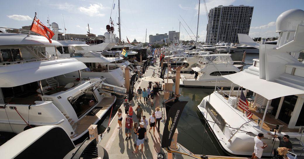 Motor yachts moored along pontoon at Palm Beach International Boat Show, visitors walking between yachts.