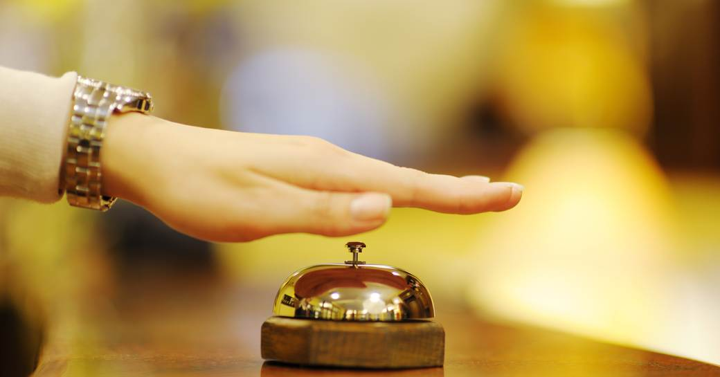 a woman's hand raised over a bell on a hotel reception desk