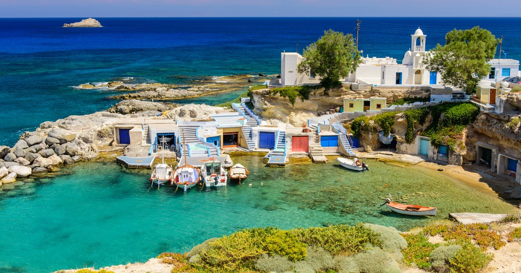 milos, an island in greece, with pretty village and little white chapel in small bay
