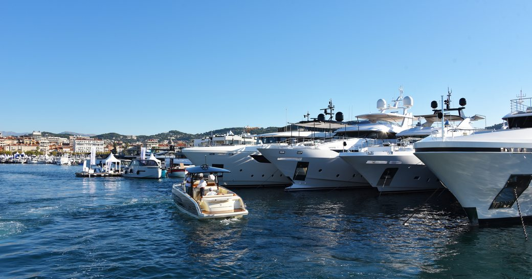 superyachts lined up at cannes yachting festival 2019, with tender cruising along in front of them