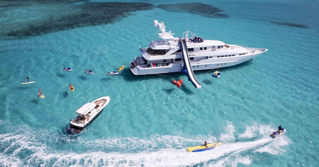crewed charter yacht At last anchored in the Caribbean with her guests using all of her waters toys on the shallow and crystalline waters