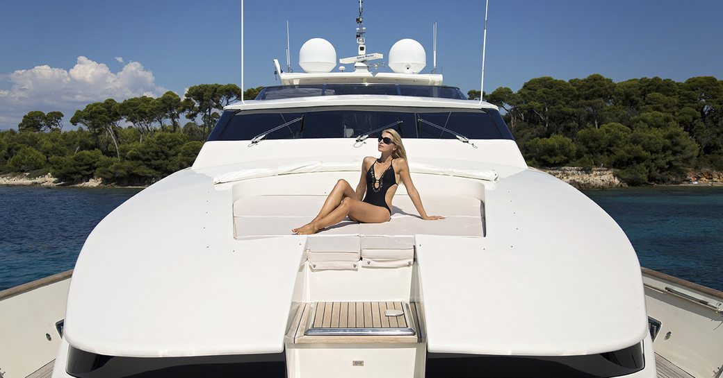 woman sits on sunpads on foredck of luxury yacht cappuccino