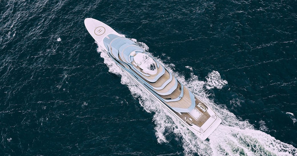 aerial shot of luxury yacht kaos, formerly known as jubilee, an oceanco yacht with blue superstructure and helipad on the foredeck