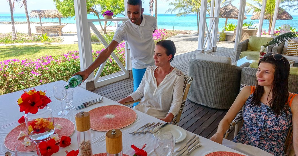 man pours drinks at alfresco dining table on thanda island
