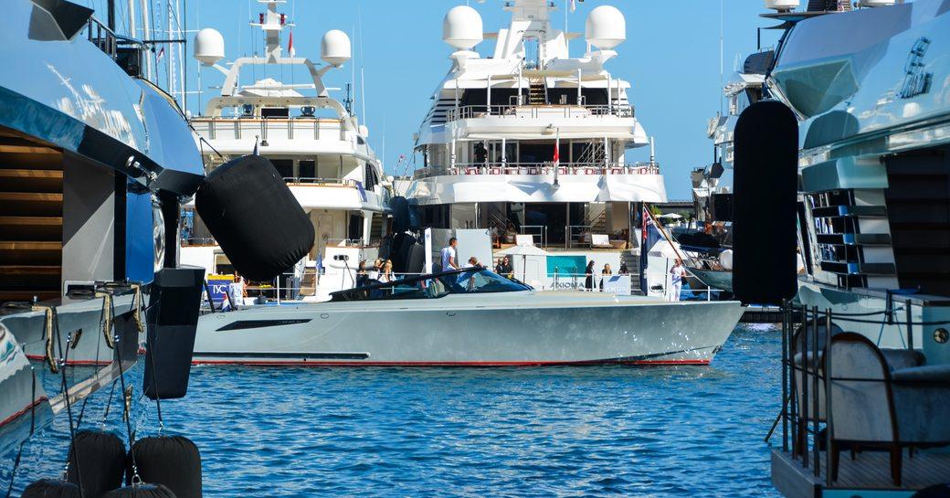 tender cruises between yachts at monaco yacht show in port hercules harbour