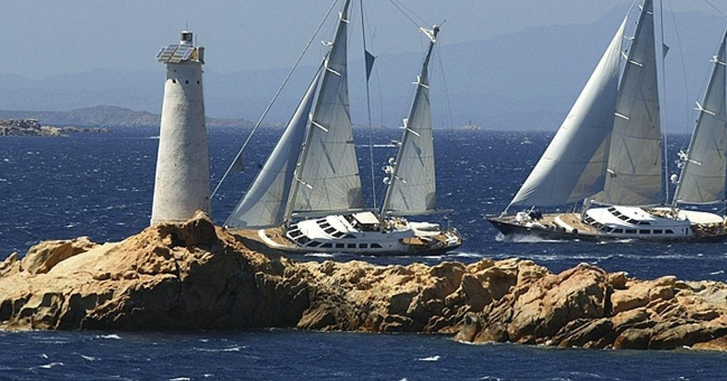 Perini Navi Cup competitors underway by lighthouse, surrounded by sea