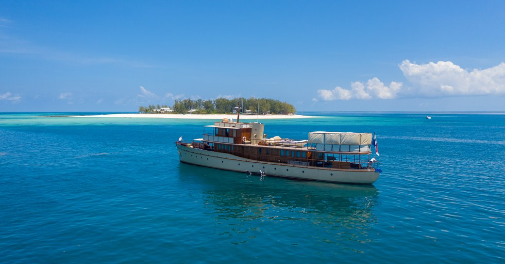 thanda private island and marine reserve with luxury yacht over the rainbow anchored nearby