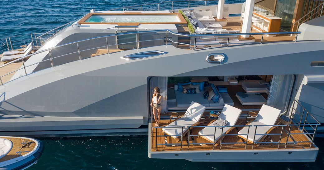 tatiana luxury yacht side balconies with furniture on the balcony and charter guest looking out to sea