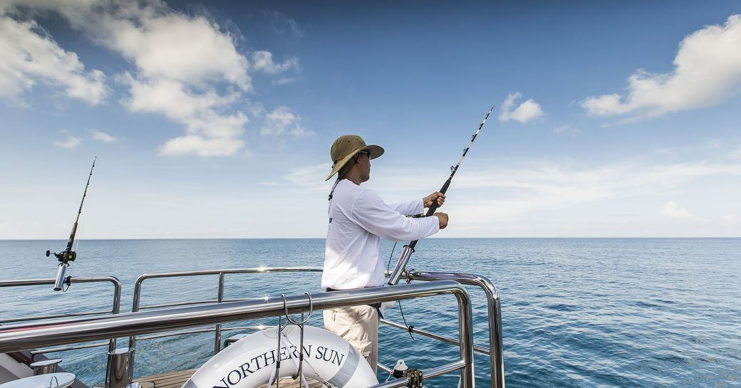 charter guest fishes off of superyacht 'Northern Sun' in South East Asia