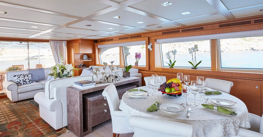 dining table and sofas in the main salon of charter yacht DEVA