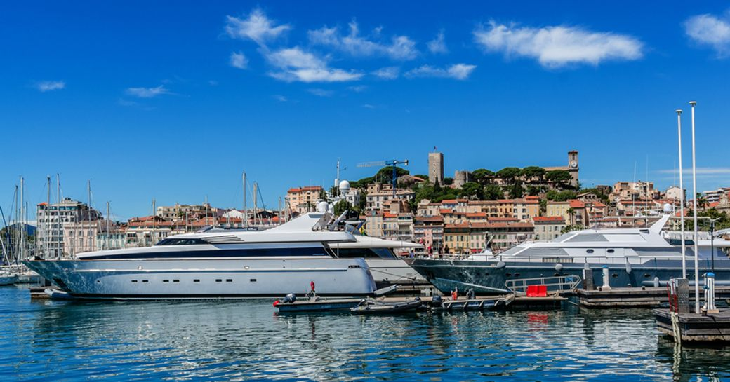 Superyachts moored in marina in front of Cannes, surrounded by sea and town of Cannes in background.