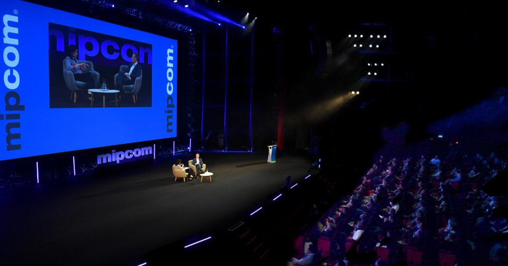 MIPCOM auditorium with a keynote speaker presenting on stage.