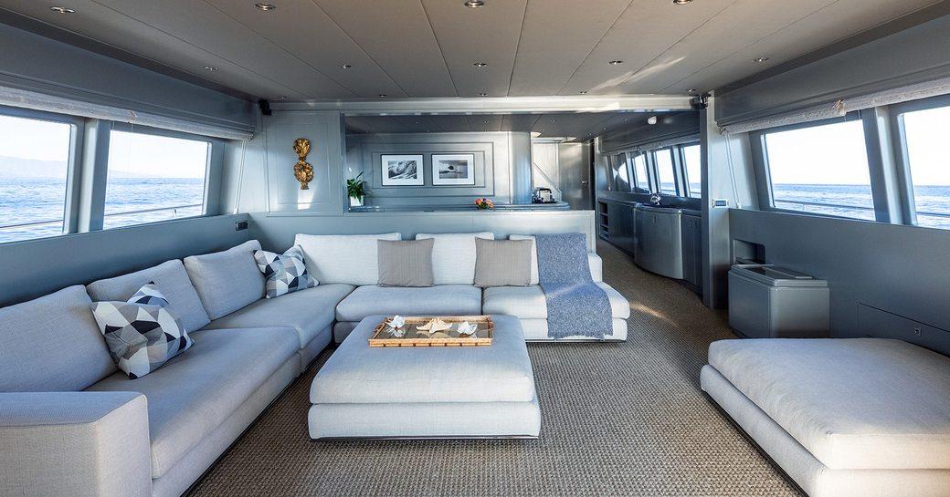 Open plan salon with sofas and ottomans on Mondo Marine motor yacht TALILA