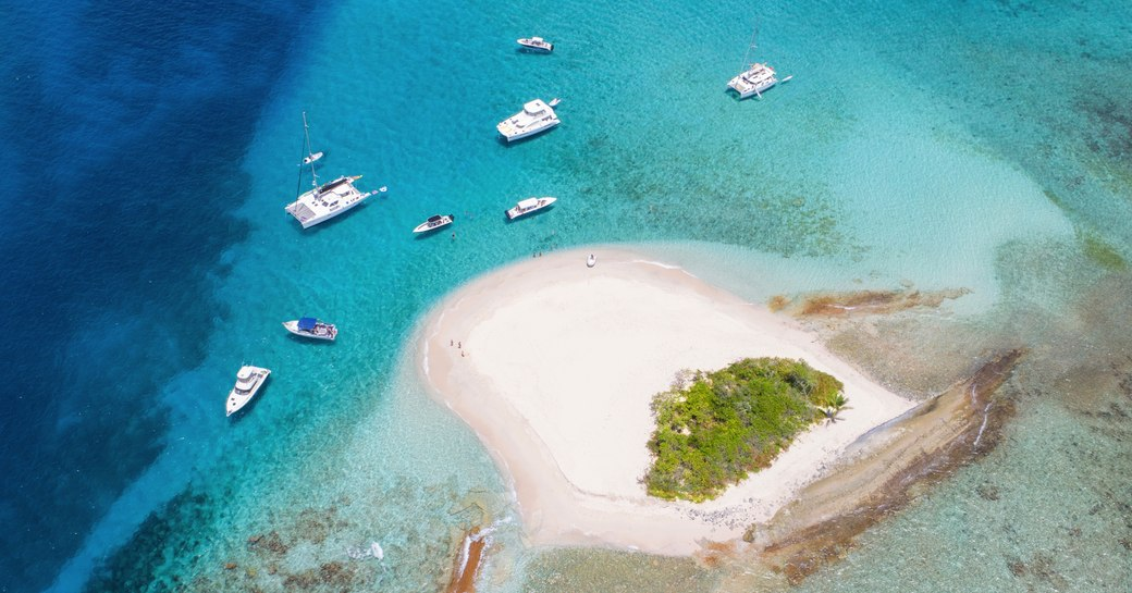Sand island with small crop of trees viewed from above and yachts in clear water around it
