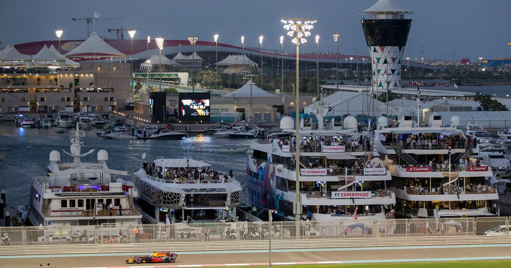 Car races along track at Abu Dhabi Grand Prix circuit at night, with superyachts lined up along the dock