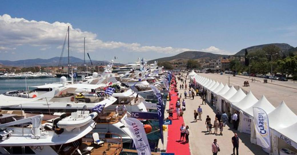 Visitors to Mediterranean Yacht Show talking to crew on red carpet, surrounded by berthed motor yachts.