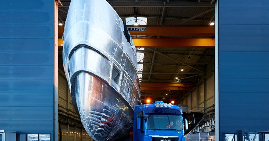 The shiny hull of Erica in the doorway to the Heesen shipyard