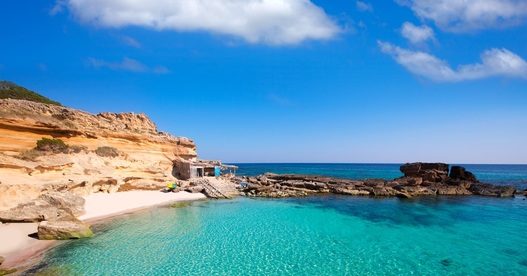 Sandy beach and clear blue sea in small bay on the island of Ibiza