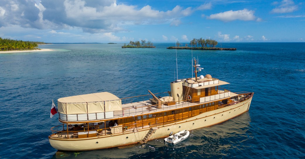 drone shot of superyacht over the rainbow on the sea in tanzania with islands in background