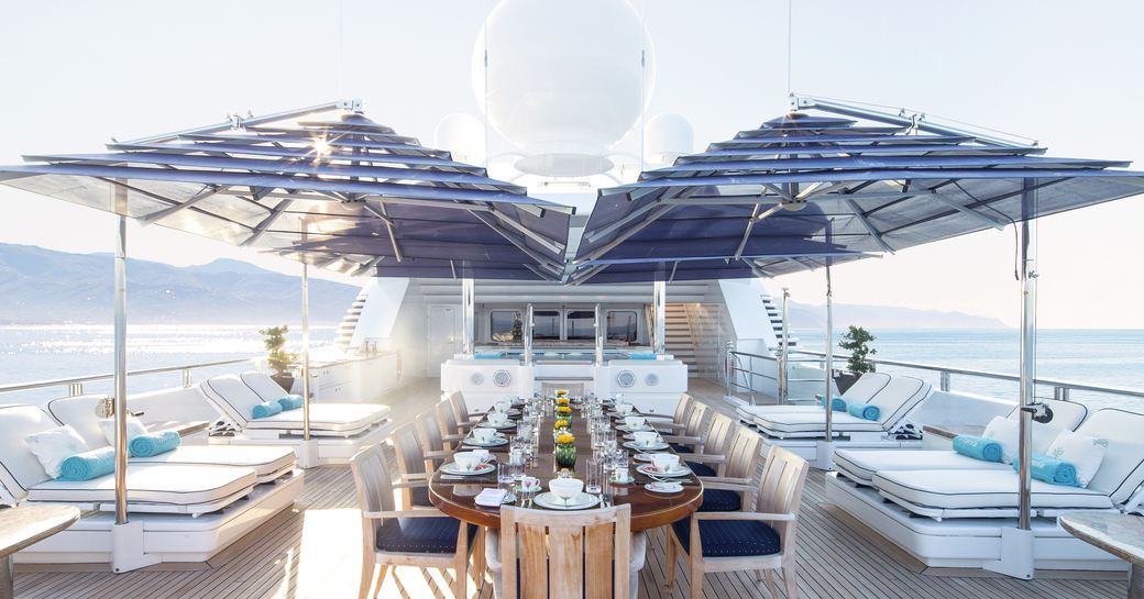 Superyacht TITANIA's upper deck, with al fresco dining, sun pads and spa pool