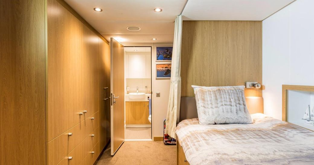 Bright interior of Game Changer yacht, showing bed and wooden furniture and door open to bathroom