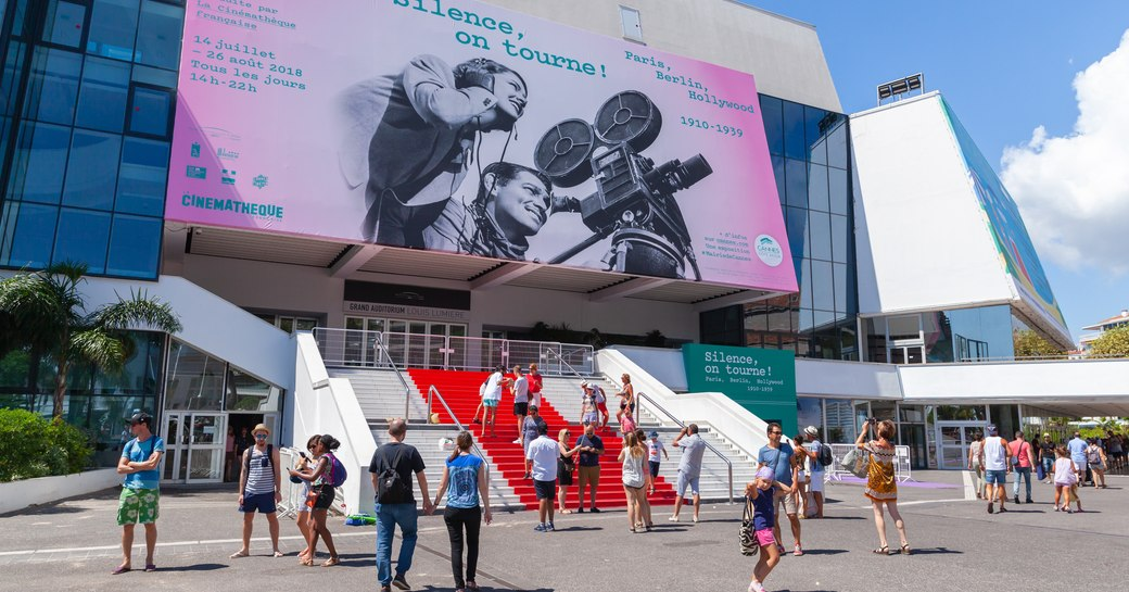 Entrance to Cannes Lions event, Palais de Festivals with red carpet on stairs and visitors gathering outside.