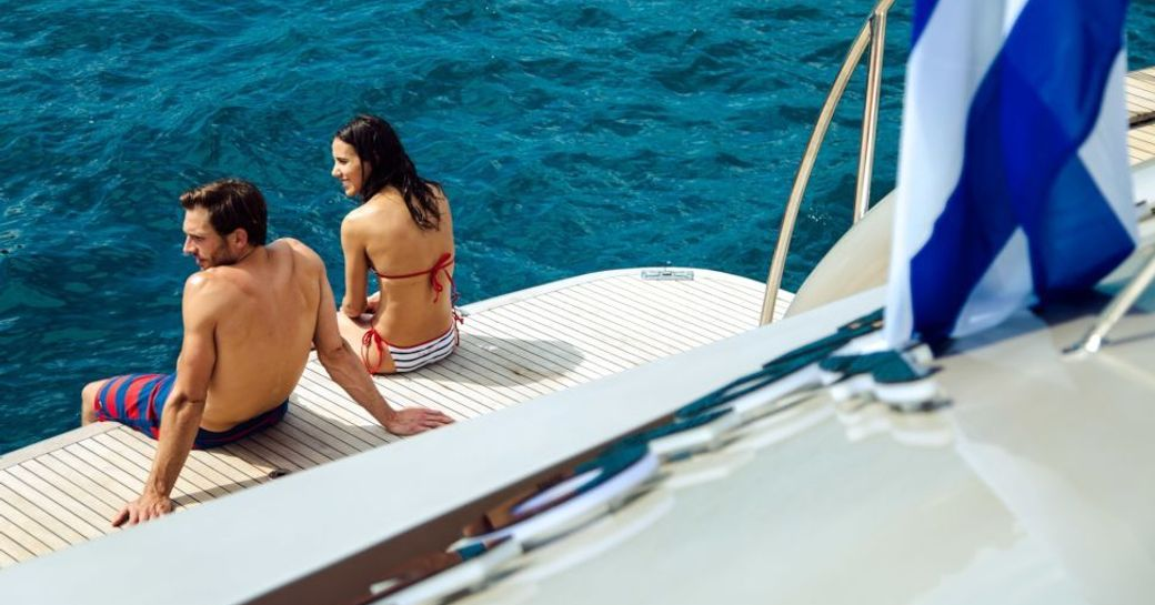 two guests sit on edge of the swim platform of superyacht PANDION with legs in the ocean