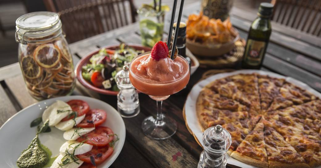 Table of food, including pizza, salad and frozen cocktails served at Diablito in Yas Marina, Abu Dhabi