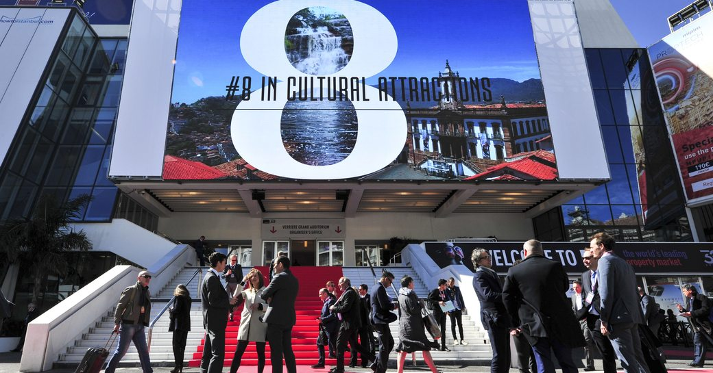 Red carpet entrance to MIPIM exhibit, with big screen overhead and visitors gathering outside.