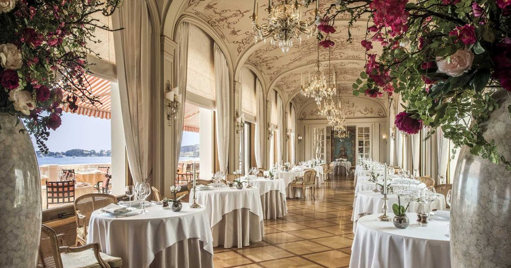 dining room of restaurant des Rois, La Réserve de Beaulieu,with white tables below arches overlooking the sea and red roses in vases