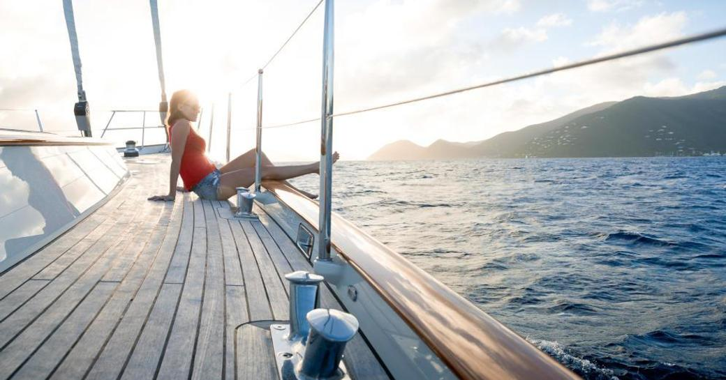 A charterer reclines on the sundeck of sailing yacht MARAE