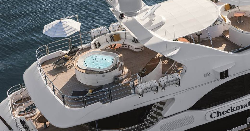 aerial view of the sundeck with a Jacuzzi, loungers and seating areas on board superyacht CHECKMATE